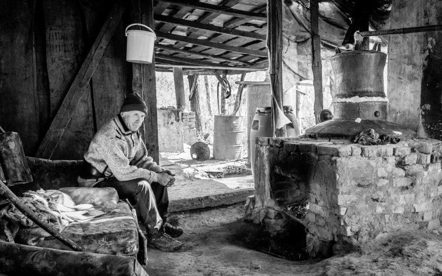 photo noir et blanc homme assis dans une distillerie de ţuica dans le Maramures, Roumanie