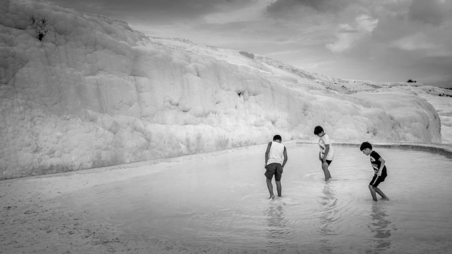 photo noir et blanc trois enfants jouent dans les eaux chaudes du site Pamukkale en Turquie